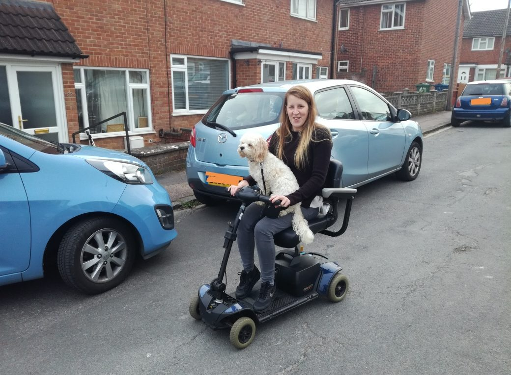 Cf patient Helen and her dog on a mobility scooter